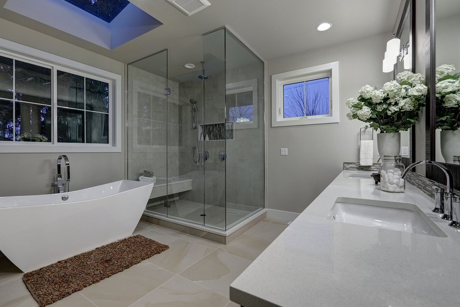 Amazing gray master bathroom with large glass walk-in shower freestanding tub and skylights on the ceiling. Northwest USA