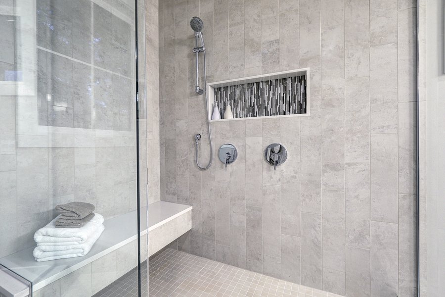 Glass walk-in shower with gray subway tiled surround accented with mosaic tile strip in wall niche of brand new home bathroom. Northwest USA