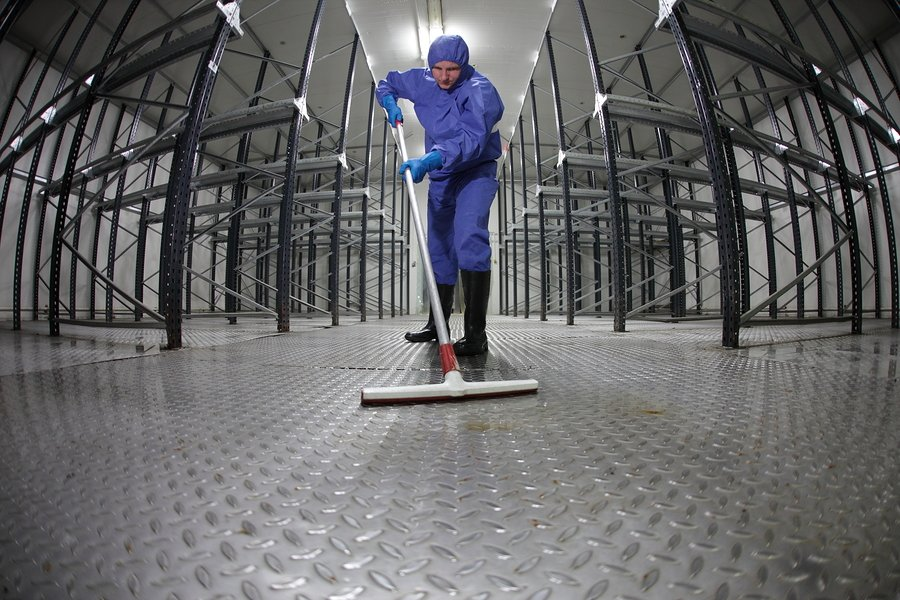 worker in protective uniform cleaning floor in empty warehouse