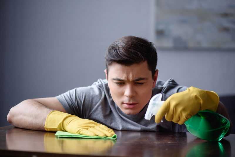 handsome man dusting table in living room with spray bottle and rag
