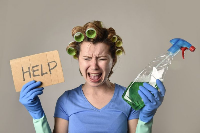 A woman with gloves and calling for help in need of a house cleaner in melbourne